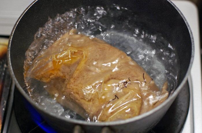 麺屋 極鶏のつけ麺のスープが封入されている袋をお湯に投入。湯煎してスープを解凍する